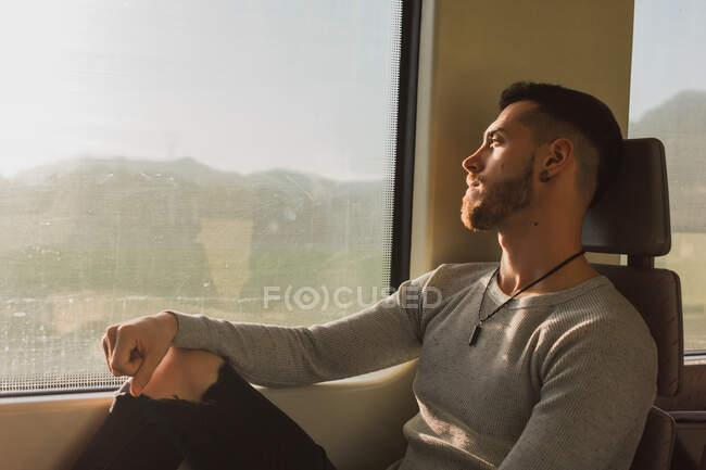 Nachdenklicher junger männlicher Fahrgast sitzt in U-Bahn-Wagen — Stockfoto
