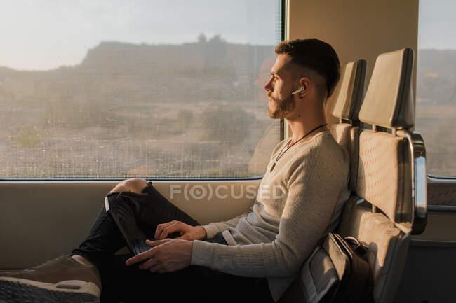 Passager masculin concentré utilisant un ordinateur portable dans le train — Photo de stock
