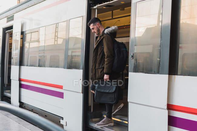 Vista lateral de un joven pasajero con mochila que llega a la estación y sale del vagón del metro - foto de stock