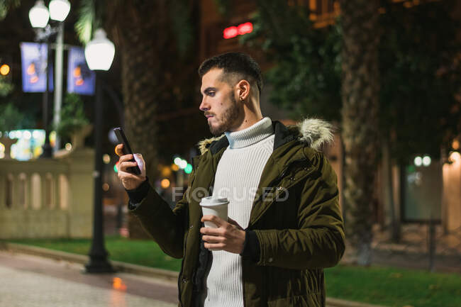 Focused youthful male with takeaway cup text messaging on cellphone while standing in street in evening — Stock Photo