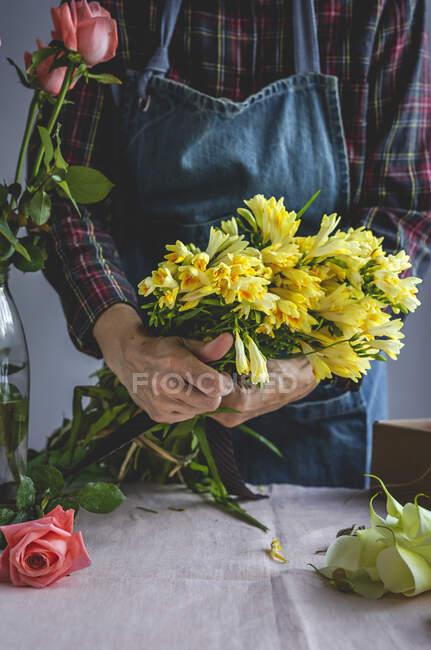 Невпізнавана жінка-професійний флорист робить букети різних типів. Троянди. Жовті квіти. Кови. — стокове фото