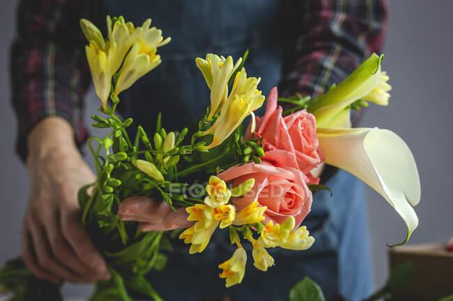 Fleuriste professionnelle féminine méconnaissable faisant des bouquets de différents types. Des roses. Fleurs jaunes. Baies — Photo de stock