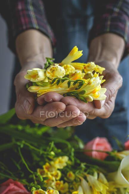 Unerkennbar weibliche professionelle Floristin, die Sträuße verschiedener Art herstellt. Rosen. Gelbe Blumen. Buchten — Stockfoto