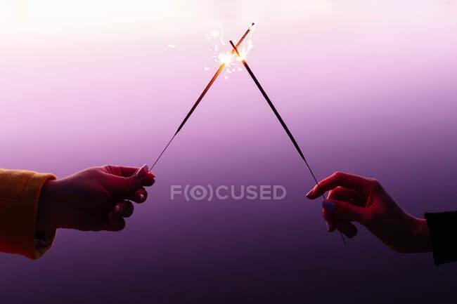 Попереду одне одного, тримаючи палаючих ігриків на барвистому фоні. — стокове фото