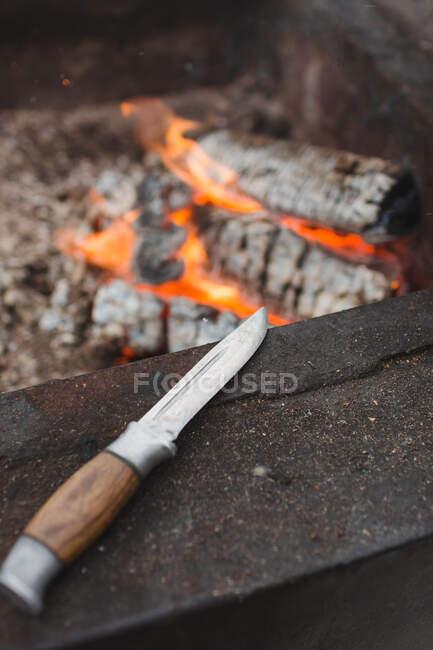 Couteau de chasse avec manche en bois placé à côté d'une cheminée en métal rouillé avec bois brûlant — Photo de stock