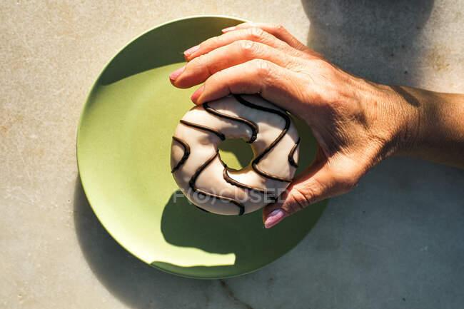 De arriba cosecha hembra sosteniendo rosquilla deliciosa con glaseado por encima del plato de cerámica verde mientras desayuna en la terraza de la cafetería en el día soleado - foto de stock