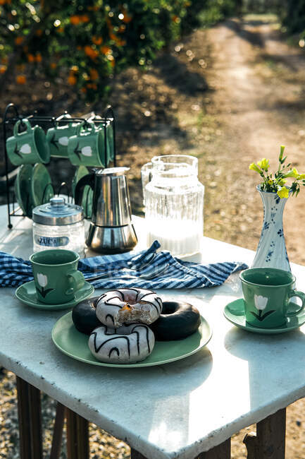 High angle of tasty donuts with icing on plate and cups of hot drink beside tableware set and moka pot — Stock Photo