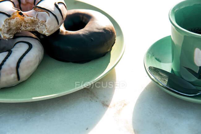 Склад ароматичного гарячого напою і смачних пончиків на столі. — стокове фото