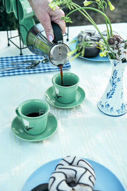 Женщина наливает горячий напиток из кофеварки в керамическую кружку во время пикника в саду — стоковое фото