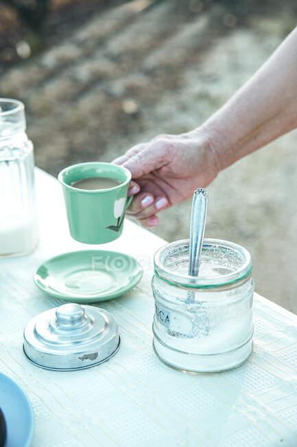 Женщина пьет вкусный кофе во время пикника в саду — стоковое фото