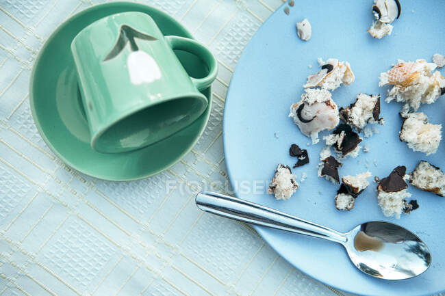 Green ceramic mug dropped on saucer and blue round plate with small crumbs of tasty pastry in composition with dirty metal teaspoon after breakfast — Stock Photo