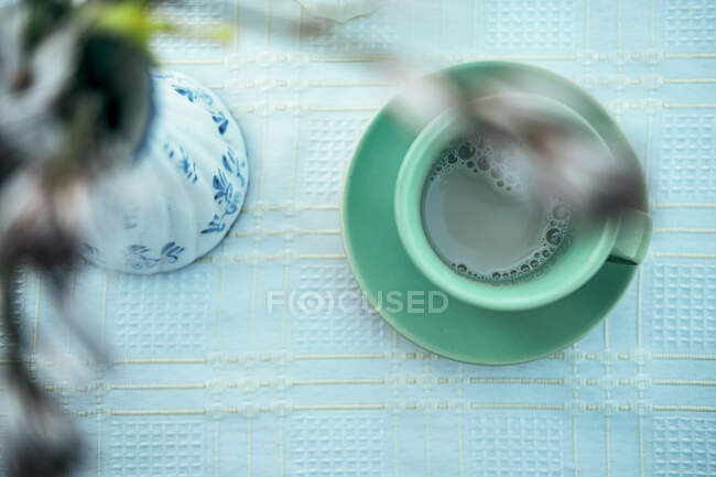 Mug of hot aromatic brown beverage with saucer on table — Stock Photo