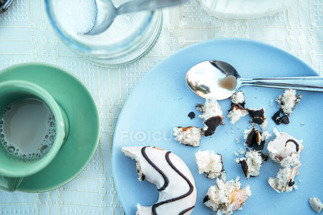 Cup of coffee and plate of pastry crumbs with spoon on table — Stock Photo