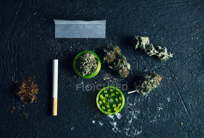 Vue en haut des bourgeons de cannabis séchés et du papier à rouler avec une cigarette sur la surface grunge — Photo de stock