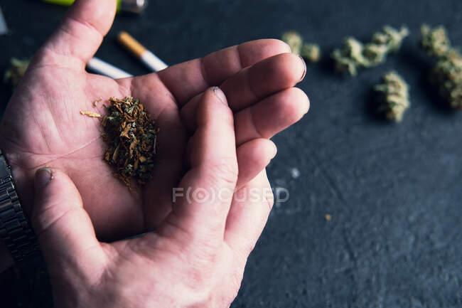 Un homme méconnaissable fait un joint de cannabis à la maison — Photo de stock
