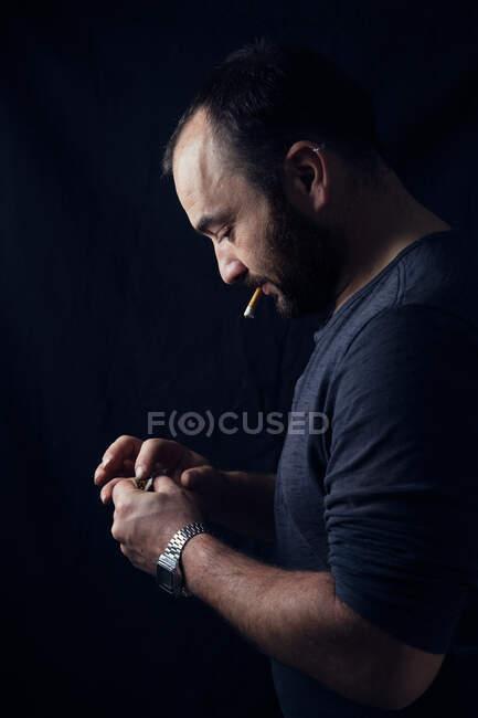 Hombre adulto haciendo hierba conjunta en la oscuridad - foto de stock