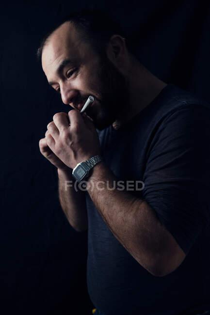 Hombre maduro concentrado lamiendo papel de liar mientras rodando cannabis romo sobre fondo negro - foto de stock