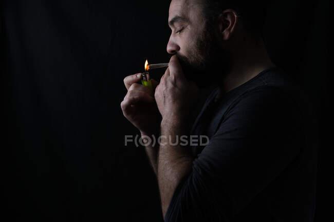 Vue latérale d'une récolte concentrée Un fumeur de sexe masculin allumant une décharge de marijuana sur fond noir — Photo de stock