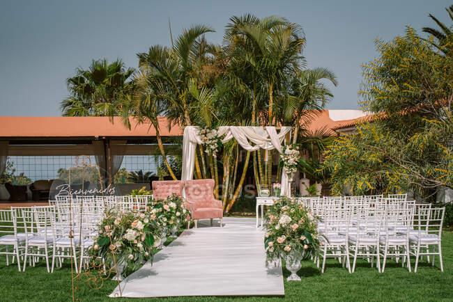 Ряды белых стульев проход среди цветов против свадебной арки на дворе зеленого тропического курорта с пальмами в солнечный день — стоковое фото