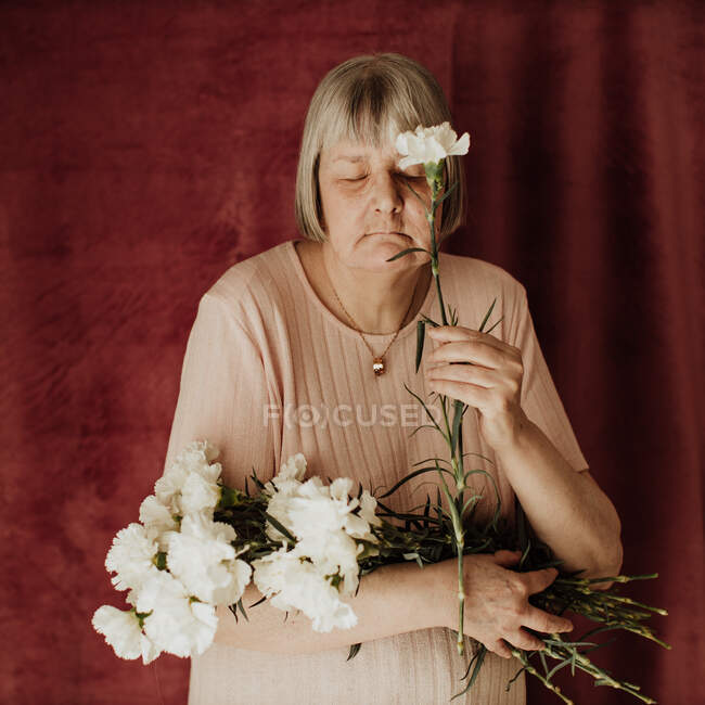 Сверху задумчивая старая женщина с седыми волосами с закрытыми глазами, держа букет белой гвоздики дома — стоковое фото