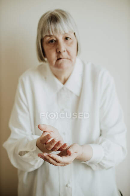 Sad elderly woman in white blouse gesturing with hands on light background looking at camera — Stock Photo