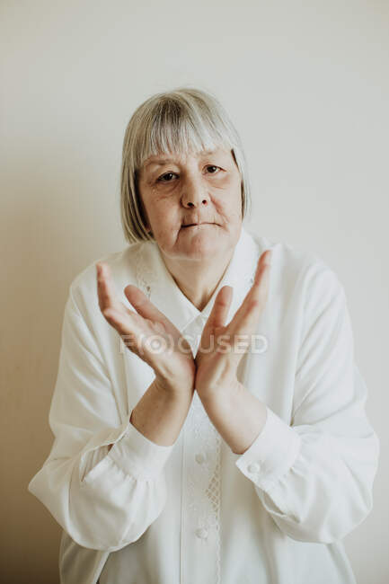 Sad elderly woman in white blouse showing disagreement while rising hands up on light background looking at camera — Stock Photo