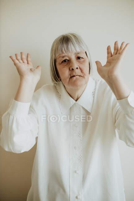 Сумна літня жінка в білій блузці показує незгоду, коли піднімається вгору на світлому фоні, дивлячись на камеру — стокове фото