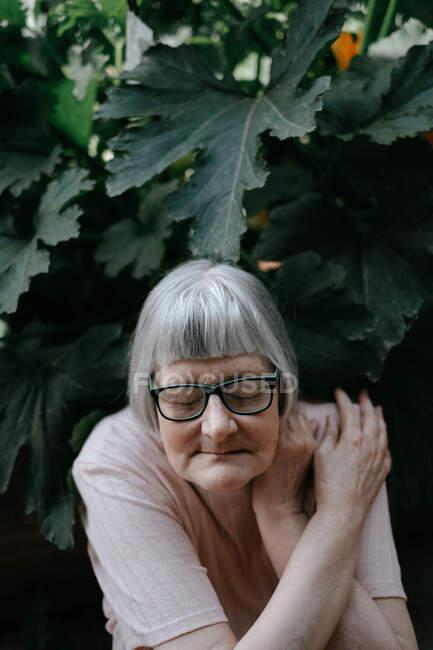 Femme âgée avec des cheveux gris et les yeux fermés dans les lunettes traversant les bras par-dessus l'épaule parmi les plantes avec de grandes feuilles vertes — Photo de stock