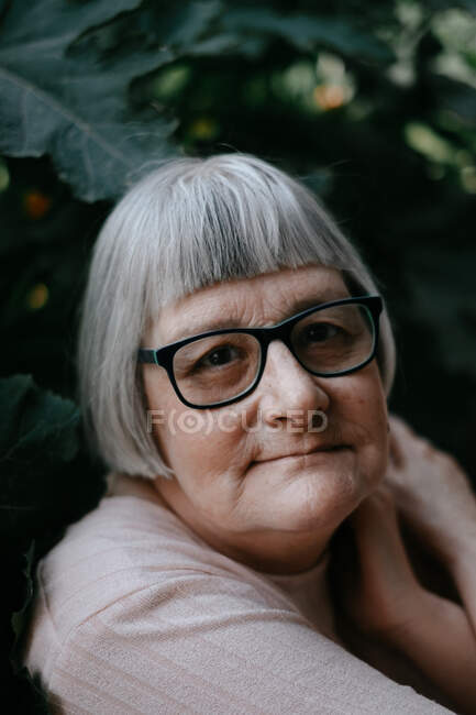 Senior woman with grey hair looking at camera in eyeglasses crossing arms over shoulder among plants with big green leafs — Stock Photo