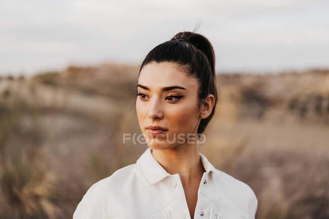Donna topless sensuale in giacca in piedi in campagna — Foto stock