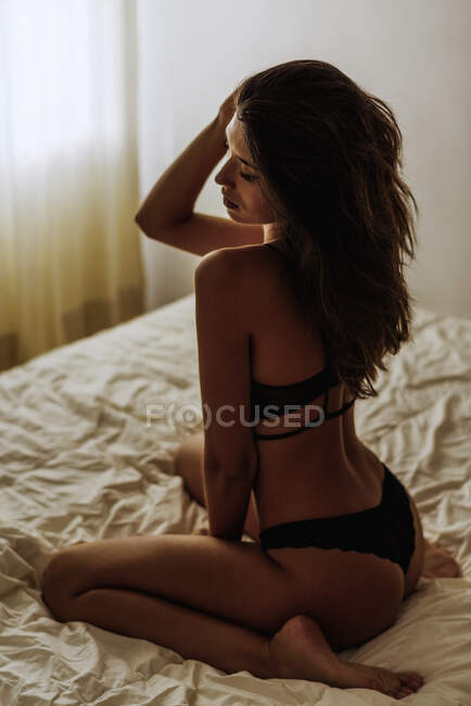 From above of young slim sensual female in black lingerie touching head and sitting provocatively on bed in morning — Stock Photo