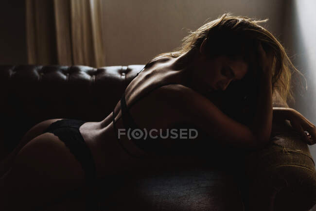 Seductive young woman in lingerie lying on sofa — Stock Photo
