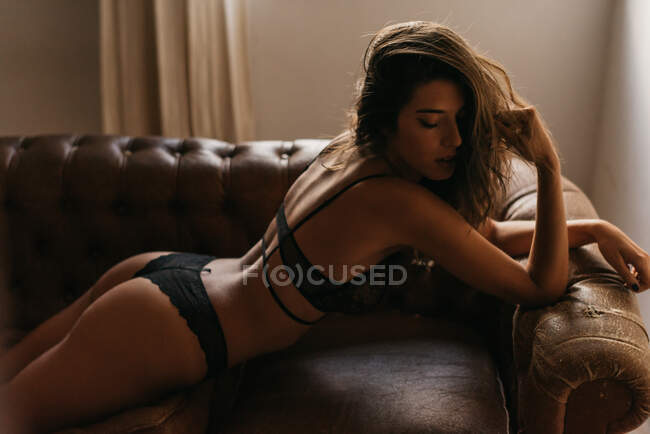 From above sensual slim young female in black lingerie lying on leather couch in apartment — Stock Photo