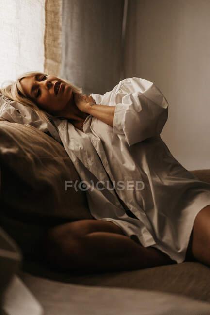 У вітальні на дивані сидить спокуслива блондинка. — стокове фото