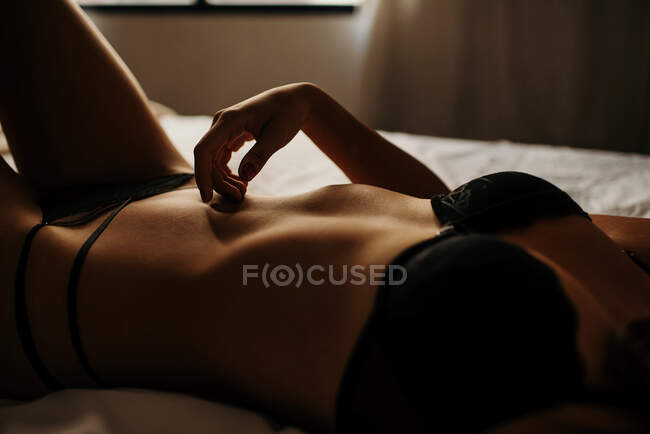 Alluring crop lady in lingerie lying on bed — Stock Photo