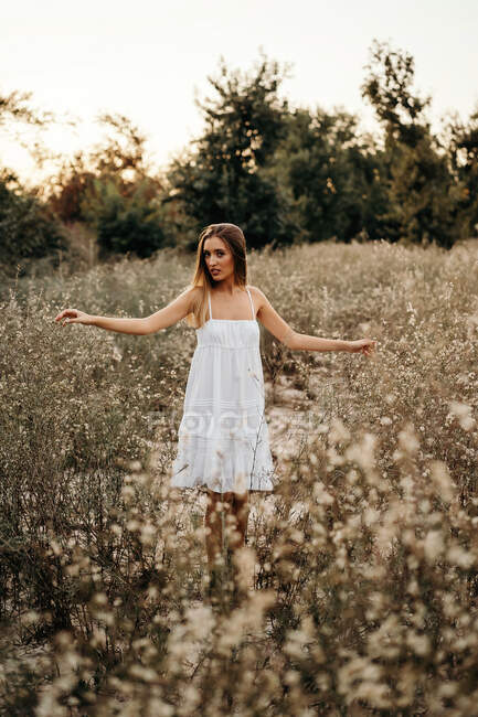 Peaceful young woman in white romantic dress standing and touching tall grass with field flowers and looking at camera — Stock Photo