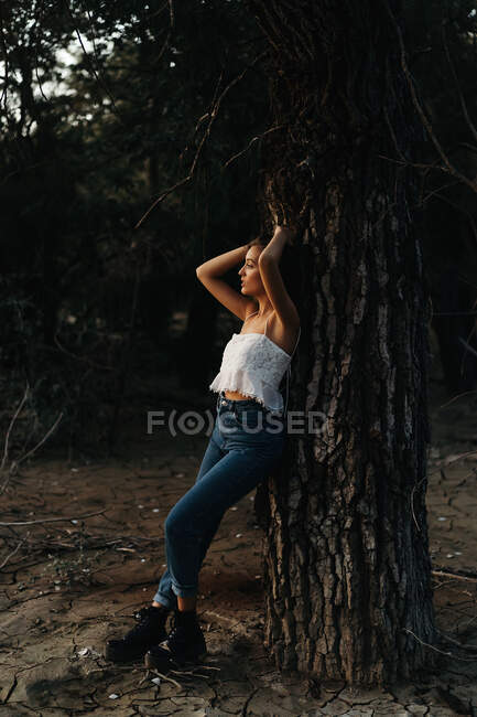 Full length of dreamy female in blue denim and white top leaning alluringly on tree looking away — Stock Photo