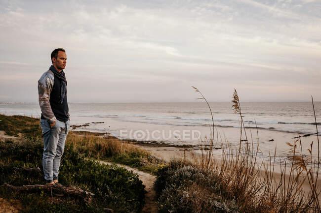 Corps complet d'un voyageur adulte adulte sérieux observant le paysage marin debout sur le littoral par temps nuageux — Photo de stock
