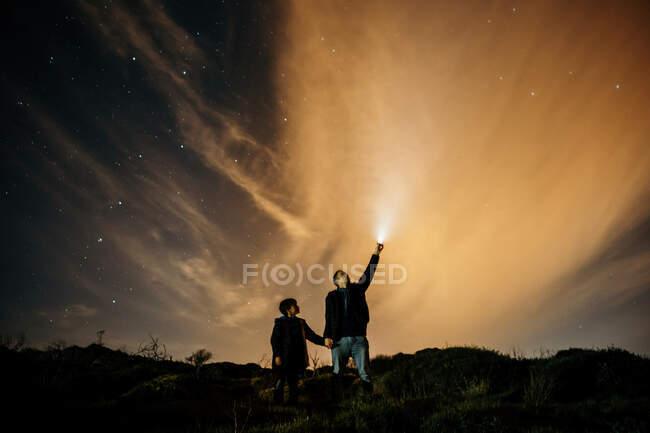 Обережно, батько і син тримаються за руки і спостерігають зоряне небо, коли дивляться вгору і освітлюють смолоскипом вночі. — стокове фото