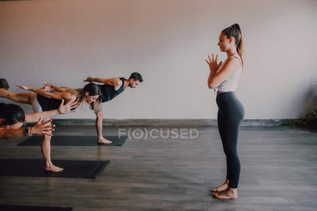 Стройная босиком женщина-инструктор в спортивной одежде стоя контрольная группа спортивных людей, концентрирующихся и делающих воин позируют три стоя на спортивных ковриках в современном зале тренировки — стоковое фото