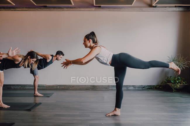 Стройная босиком женщина-инструктор в спортивной одежде стоя в воин представляют три и контрольная группа спортивных людей, концентрирующихся и делая те же упражнения стоя на спортивных ковриках в современной тренировочной комнате — стоковое фото