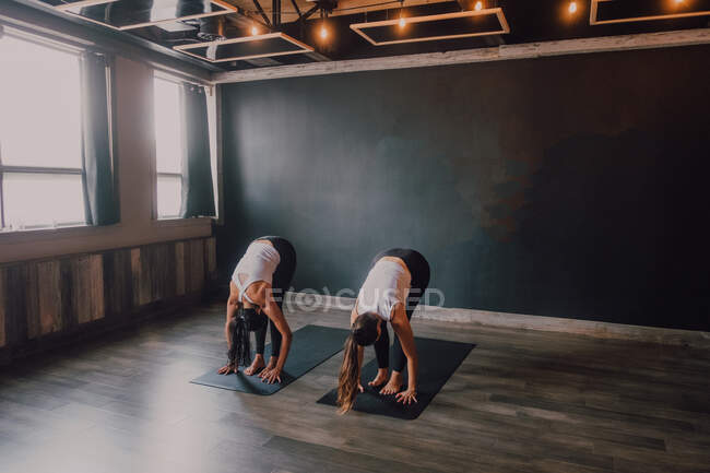 Сосредоточьтесь босиком на неизвестных женщинах в спортивной одежде и занимайтесь упражнениями на спортивные коврики на деревянном полу против белых стен просторного зала — стоковое фото