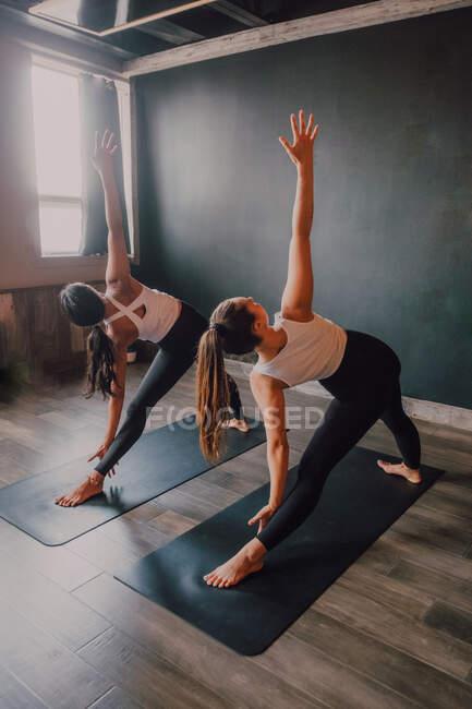 Задний вид неузнаваемых женщин, делающих позу треугольника, стоящих на спортивных ковриках в современной тренировочной комнате — стоковое фото