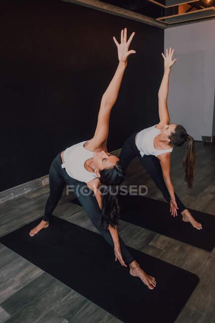 Женщины, делающие позу треугольника, стоят на спортивных ковриках в современной тренировочной комнате — стоковое фото