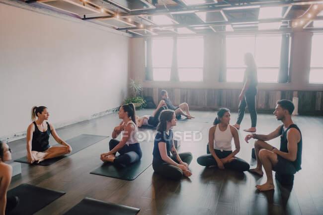 Высокий угол юных женщин и мужчин в спортивной одежде, сидящих в позе лотоса и интересующихся дискуссиями во время отдыха после групповых тренировок в современной студии йоги — стоковое фото
