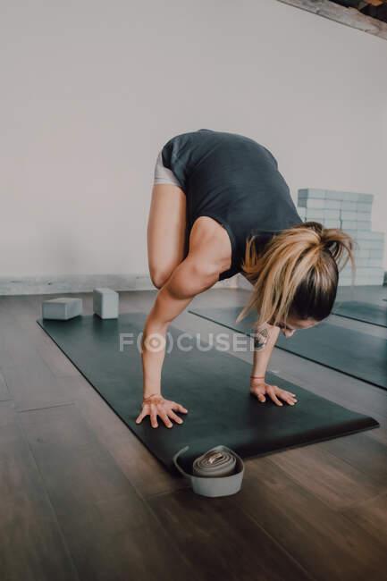 Обратный вид вверх ногами неузнаваемой спортсменки в спортивной одежде, практикующей йогу в позиции бакасана на черном спортивном коврике в просторной современной студии — стоковое фото