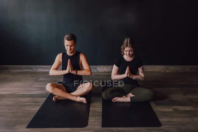 Спокойная молодая женщина и мужчина в спортивной одежде с закрытыми глазами и скрещенными ногами медитируют вместе, сидя в позе падмасаны напротив задней стены в современной студии йоги — стоковое фото