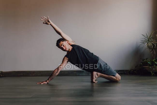 Трудолюбивый босоногий спортсмен в спортивной одежде практикующий йогу на деревянном полу в просторной современной тренировочной комнате — стоковое фото