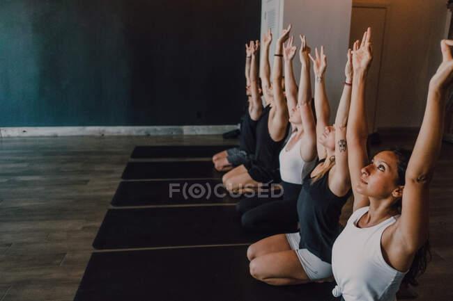 Высокий угол группы молодых спортивных женщин и мужчин в спортивной одежде с поднятыми руками и Гьян Мудра растягивая тело и медитируя, сидя в позе вирасаны на спортивных ковриках и глядя вверх тренировки в современной студии йоги — стоковое фото