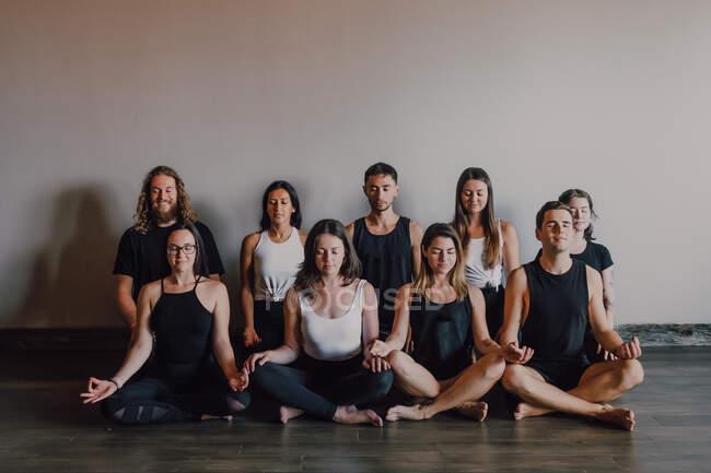 Hohe Gruppe junger, gelassener Frauen und Männer in Sportbekleidung mit geschlossenen Augen und Gyan Mudra, der sich entspannt und meditiert, während er in Padmasana-Position vor weißer Wand im modernen Yogastudio sitzt — Stockfoto